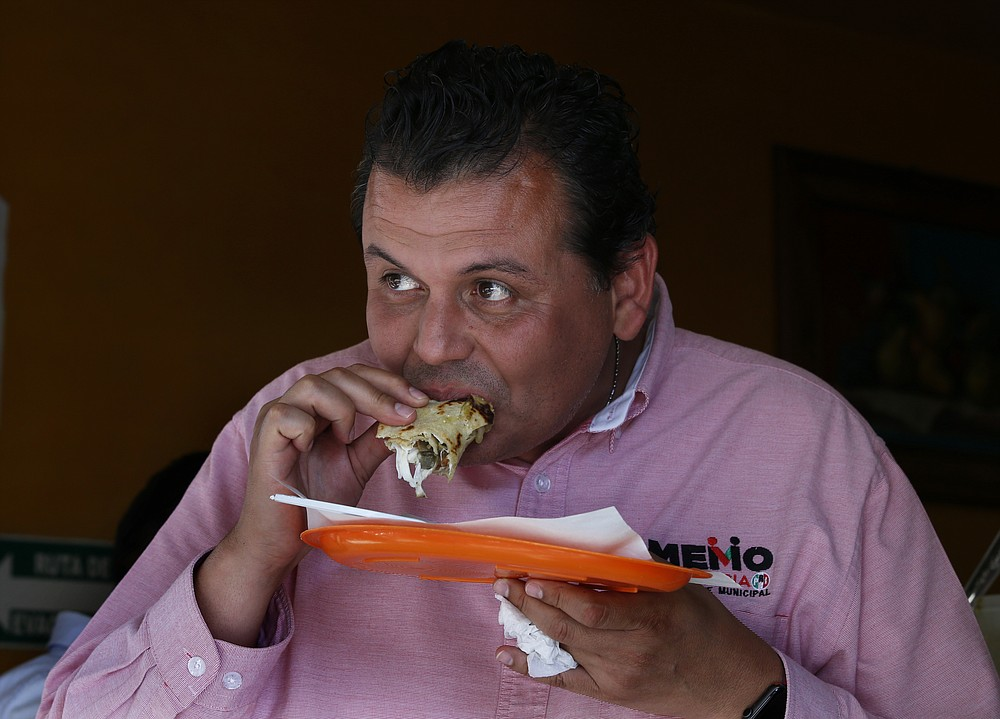 Mayoral candidate Guillermo Valencia eats a taco during a campaign stop at a market in Morelia, Michoacan state, Mexico, Friday, May 21, 2021. Valencia is the leader of a crime victims' advocacy group and a former legislator who is running for mayor on the ticket of the former ruling Institutional Revolutionary Party. He also once served as mayor of his hometown of Tepalcatepec, near the border with Jalisco state. (AP Photo/Marco Ugarte)