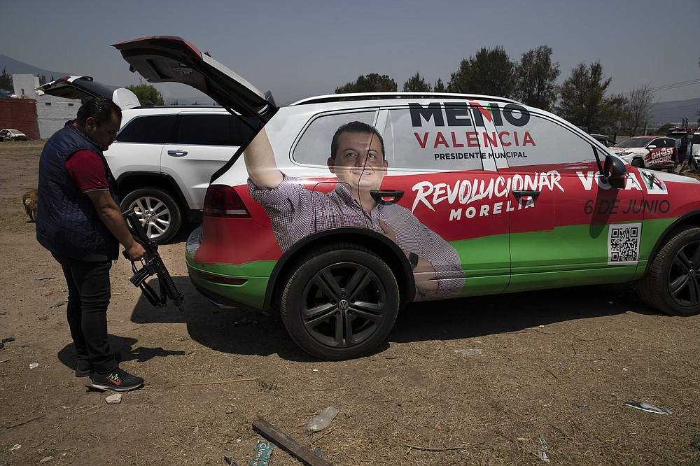 One of the bodyguards that acts as the driver of Institutional Revolutionary Party, PRI, mayoral candidate Guillermo Valencia, grabs his assault rifle from the back of the armored SUV they travel in, during one of Valencia's campaign stops in Morelia, Michoacan state, Mexico, Saturday, May 22, 2021. The armored vehicle was loaned to Valencia by a friend after he was attacked by gunmen on May 8. (AP Photo/Marco Ugarte)