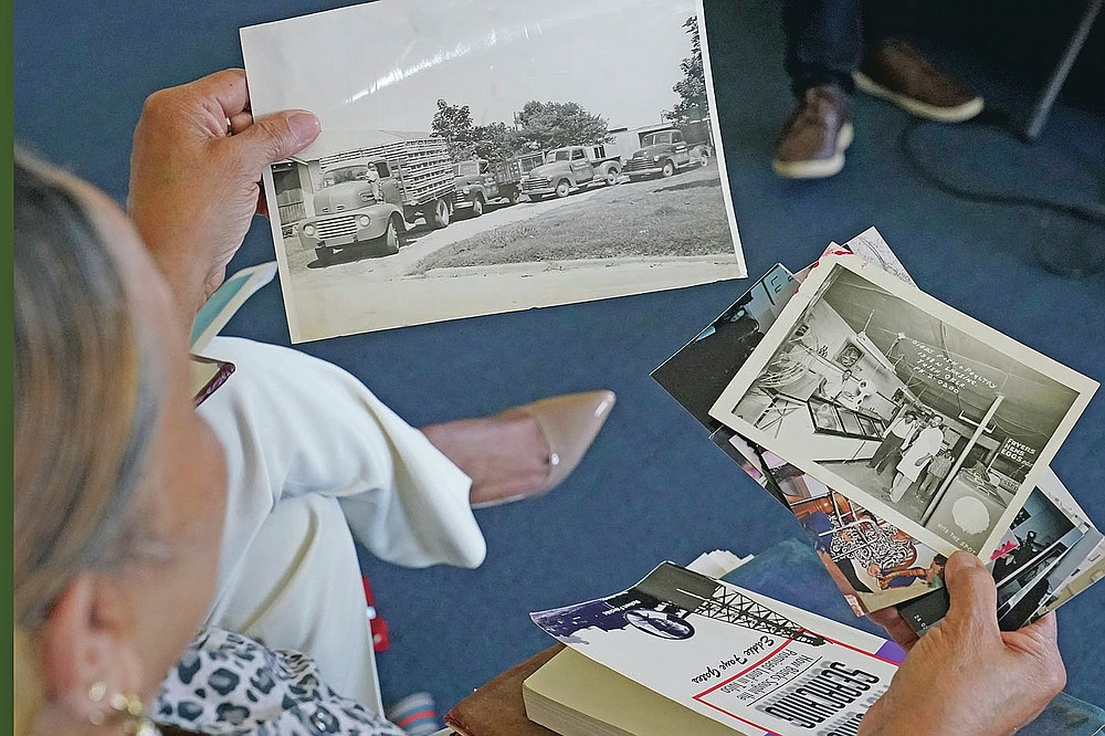 Carolyn Roberts, daughter of Tulsa Race Massacre survivor Ernestine Alpha Gibbs, holds photos of the Gibbs' former family businesses during an interview in Tulsa, Okla., on Sunday, April 11, 2021. Today, the Gibbs Next Generation Center, a small shopping mall and office park run by descendants of Ernestine, is located on the property which used to be the location of the businesses run by Roberts' parents. (AP Photo/Sue Ogrocki)