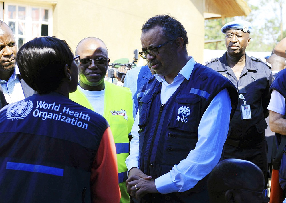 """FILE - In this Friday, Aug. 10, 2018 file photo, Dr. Tedros Adhanom Ghebreyesus, WHO Director General, centre, speaks to a health official at a newly established Ebola response center in Beni, Democratic Republic of Congo. The head of the World Health Organization acknowledged the U.N. agency's response to allegations of sexual abuse perpetrated by its own staffers during an Ebola outbreak in Congo was """"slow"""" after being pressed on the issue by numerous countries following an Associated Press investigation that revealed senior management were informed about sexual misconduct complaints. (AP Photo/Al-hadji Kudra Maliro, FIle)"""