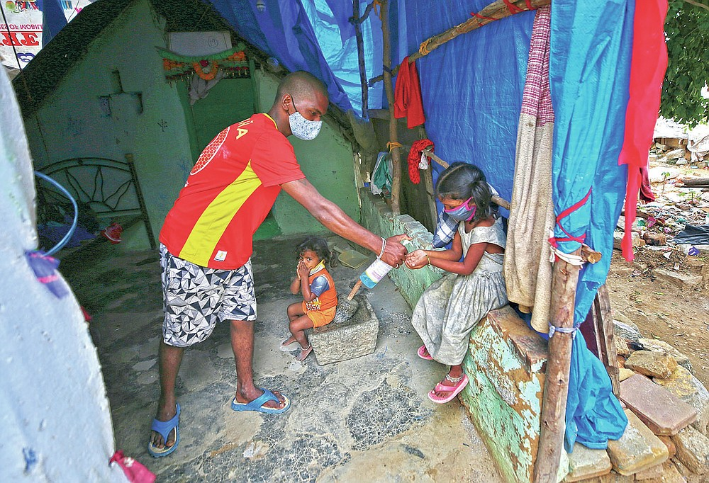Gangaiah, son of Padmavathi who died of COVID-19, gives sanitizer to his elder daughter Shanti as two-year-old Priya looks on inside their family hut which is made from bamboo and plastic sheeting at a slum in Bengaluru, India, Thursday, May 20, 2021. Padmavathi collected hair, taking it from women's combs and hairbrushes to later be used for wigs. She earned about $50 a month. (AP Photo/Aijaz Rahi)