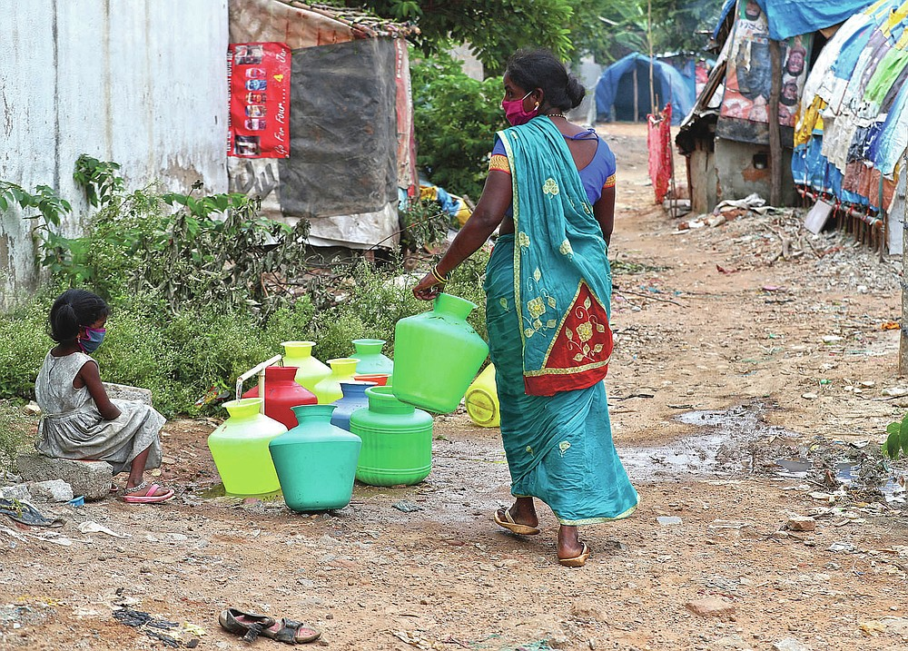 Five-year-old Shanthi, left, granddaughter of Padmavathi who died of COVID-19, collects potable water at a public tap near her family hut at a slum in Bengaluru, India, Thursday, May 20, 2021. Padmavathi collected hair, taking it from women's combs and hairbrushes to later be used for wigs. She earned about $50 a month. (AP Photo/Aijaz Rahi)