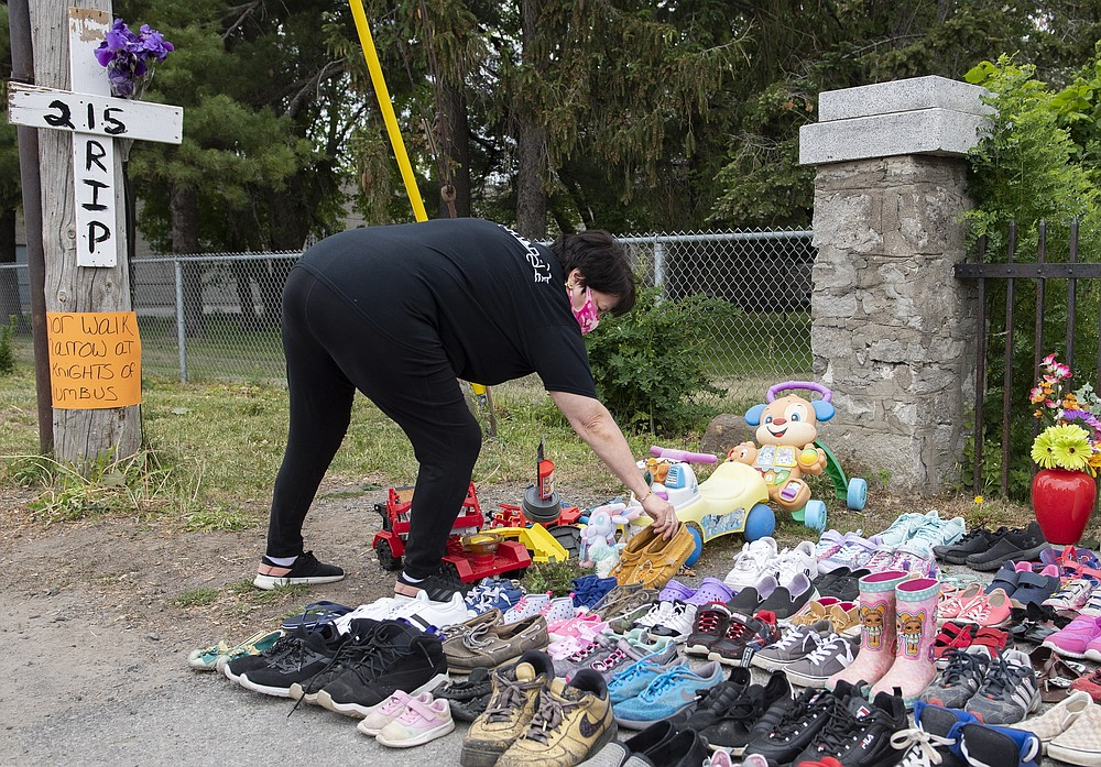 A woman places children's moccasins as a tribute to all the victims of the residential school system outside St. Francis Xavier Church in Kahnawake, Quebec, Sunday, May 30, 2021. (Graham Hughes/The Canadian Press via AP)