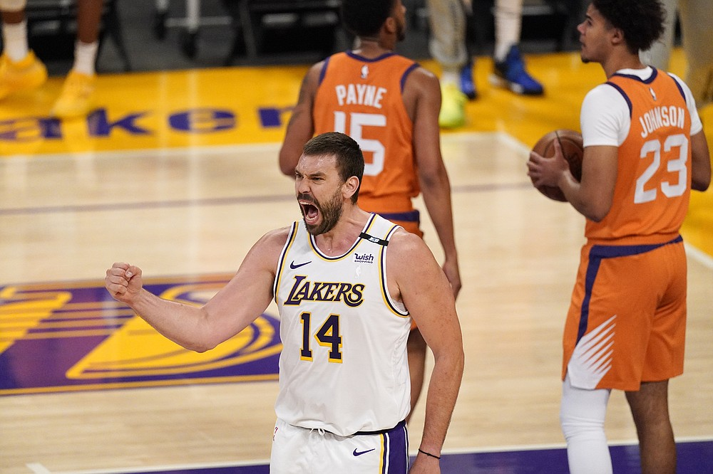 Los Angeles Lakers center Marc Gasol, left, celebrates after scoring as Phoenix Suns guard Cameron Payne, center, and forward Cameron Johnson stand in the background during the first half in Game 4 of an NBA basketball first-round playoff series Sunday, May 30, 2021, in Los Angeles. (AP Photo/Mark J. Terrill)
