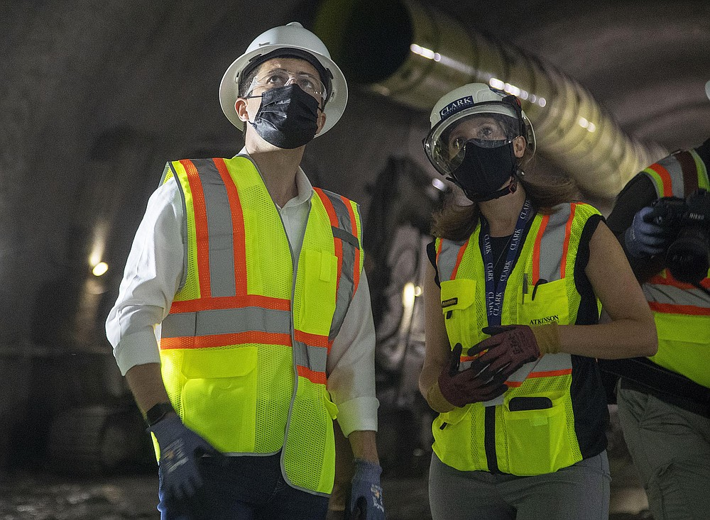 Construction project manager Gabrielle Ferro, second right, speaks with U.S. Secretary of Transportation Pete Buttigieg, during a tour of an underground tunnel for the expansion of the Hartsfield–Jackson Atlanta International Airport plane train tunnel at the Hartsfield–Jackson Atlanta International Airport, Friday, May 21, 2021, in Atlanta. (Alyssa Pointer/Atlanta Journal-Constitution via AP)