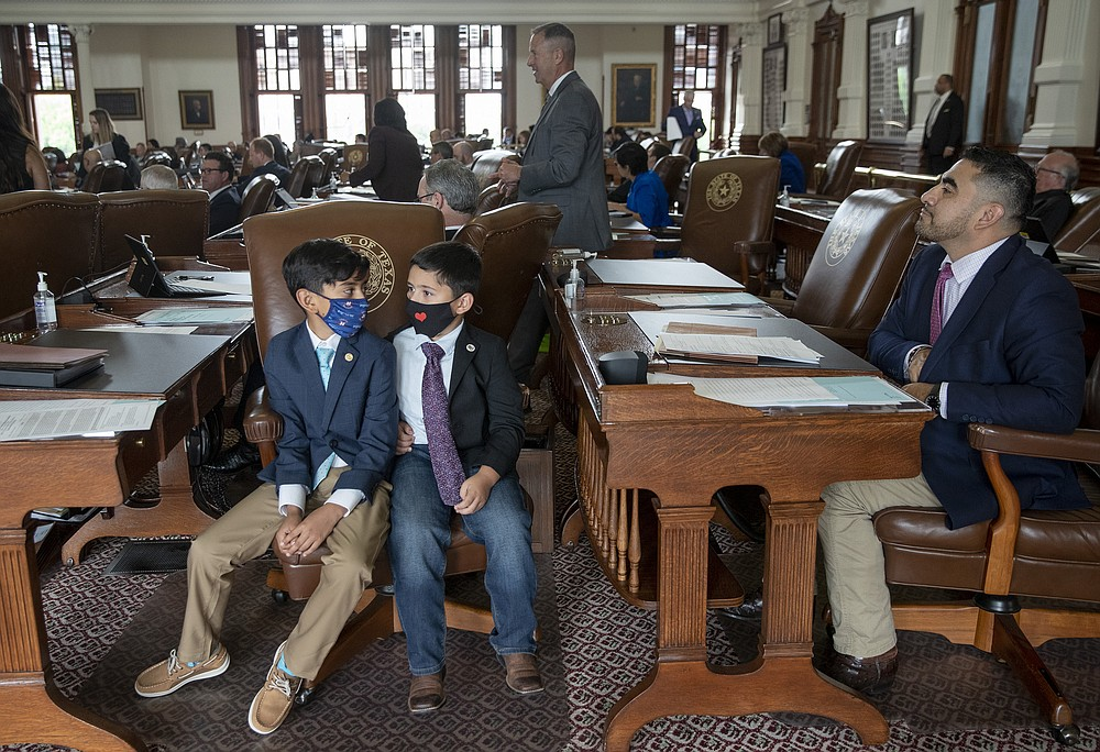 Armando Walle, 10, left, and his brother Joaquin Walle accompany their father, State Representative Armando Walle, D-Houston, right, on the floor of the House on the Capitol, the penultimate day of the 87th Texas Legislature, Sunday May 30, 2021 (Jay Janner / Austin American-Statesman via AP)