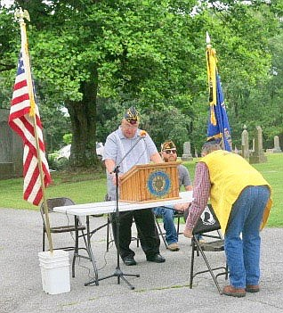 Westside Eagle Observer/SUSAN HOLLAND Mark Russow, vice-commander of John E. Tracy American Legion Post 25 at Gravette, places the POW/MIA banner on the back of the empty chair which is a standard feature at every American Legion meeting, while post chaplain Jheri Roberts explains the significance of the tradition.