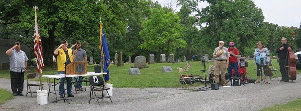 """Westside Eagle Observer/SUSAN HOLLAND   Jheri Roberts, post chaplain of John E. Tracy American Legion Post 25 at Gravette; post member Al Blair and speaker Matt McClain, stand at attention and salute and members of the Old Town String Band also stand at attention as the poignant strains of """"Taps"""" are played at the conclusion of Memorial Day services at Hillcrest Cemetery."""