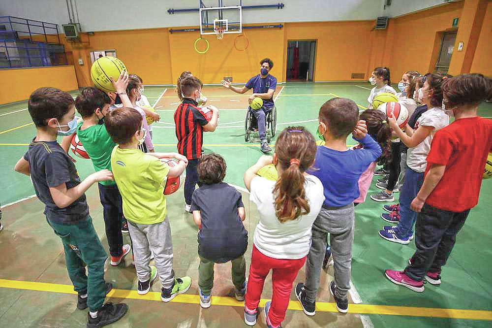 Adolfo Damian Berdun, of Argentina, a professional player and captain of the Argentine basketball Paralympic team, teaches children basketball at a primary school in Verano Brianza, outskirt of Milan, Italy, Tuesday, May 11, 2021. Four second-grade classes in the Milan suburb of Verano Brianza have been learning to play basketball this spring from a real pro. They also getting a lesson in diversity. Their basketball coach for the last month has been Adolfo Damian Berdun, an Argentinian-Italian wheelchair basketball champion. Berdun, 39, lost his left leg in a traffic accident at ag 13 in his native Buenos Aires, and he has visited many schools over the years to discuss how he has lived with his disability. (AP Photo/Luca Bruno)