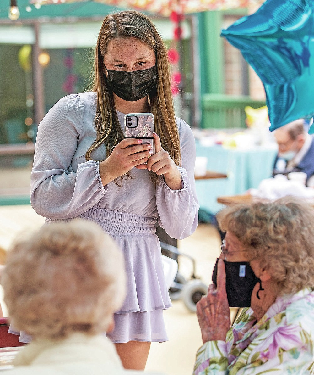 Sidney Smith makes a photo of pen pals at a reception for the Grimsley Pen Pal Club at Heritage Greens Senior Living in Greensboro, N.C., on Sunday, May 16, 2021. Smith founded the Penpal Club at Grimsley.   (Woody Marshall/News & Record via AP)
