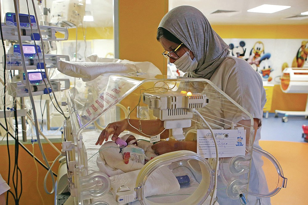 A Moroccan nurse is caring for one of nine newborns housed in an incubator at a private clinic in Ain Borja, Casablanca, Masoko, on Wednesday, May 5, 2021.  They waited only seven, the Mali Ministry of Health announced on Wednesday.  Halima Sisson, 25, gave birth by caesarean section after receiving special care in Morocco, the ministry said.  (AP Photo / Abdeljalil Bounhar)