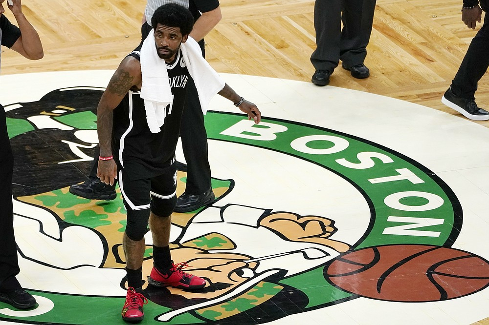 Brooklyn Nets guard Kyrie Irving scrapes his foot on the Boston Celtics logo at mid-court after they defeated the Celtics  in Game 4 during an NBA basketball first-round playoff series, Sunday, May 30, 2021, in Boston. (AP Photo/Elise Amendola)