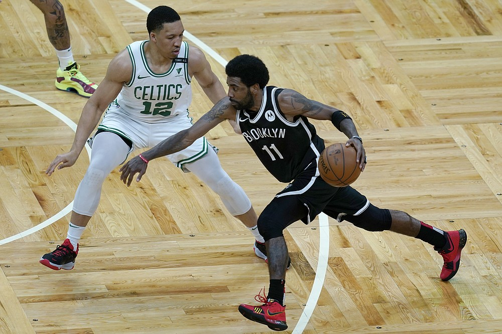Brooklyn Nets guard Kyrie Irving (11) drives against Boston Celtics forward Grant Williams (12) in the first half of Game 4 during an NBA basketball first-round playoff series, Sunday, May 30, 2021, in Boston. (AP Photo/Elise Amendola)