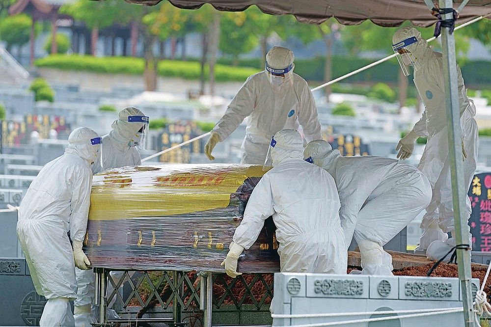 Health workers wearing Personal Protective Equipment (PPE) carry a coffin during the funeral for a COVID-19 victim at Nirvana memorial, a Buddhist, Taoist and Christian cemetery in Semenyih, Malaysia, Wednesday, May 26, 2021. Malaysia's latest coronavirus surge has been taking a turn for the worse as surging numbers and deaths have caused alarm among health officials, while cemeteries in the capital are dealing with an increasing number of deaths. (AP Photo/Vincent Thian)