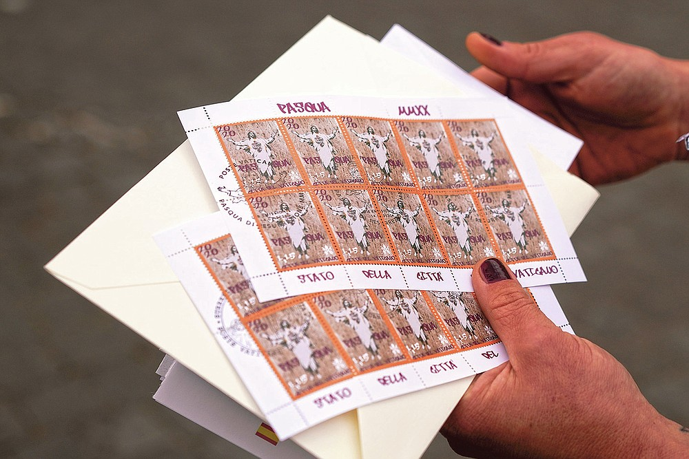 Artist Alessia Babrow shows the Vatican stamps during an interview with the Associated Press, at the Vatican, Friday, May 14, 2021. Babrow sued the Vatican City State's telecommunications office in a Rome court last month, saying it was wrongfully profiting off her creativity and violating the original intent of her artwork. The lawsuit, which is seeking nearly 130,000 euro in damages, said the Vatican had ignored Babrow's attempts to negotiate a settlement after she discovered it had reproduced her poster art unlawfully. (AP Photo/Andrew Medichini)