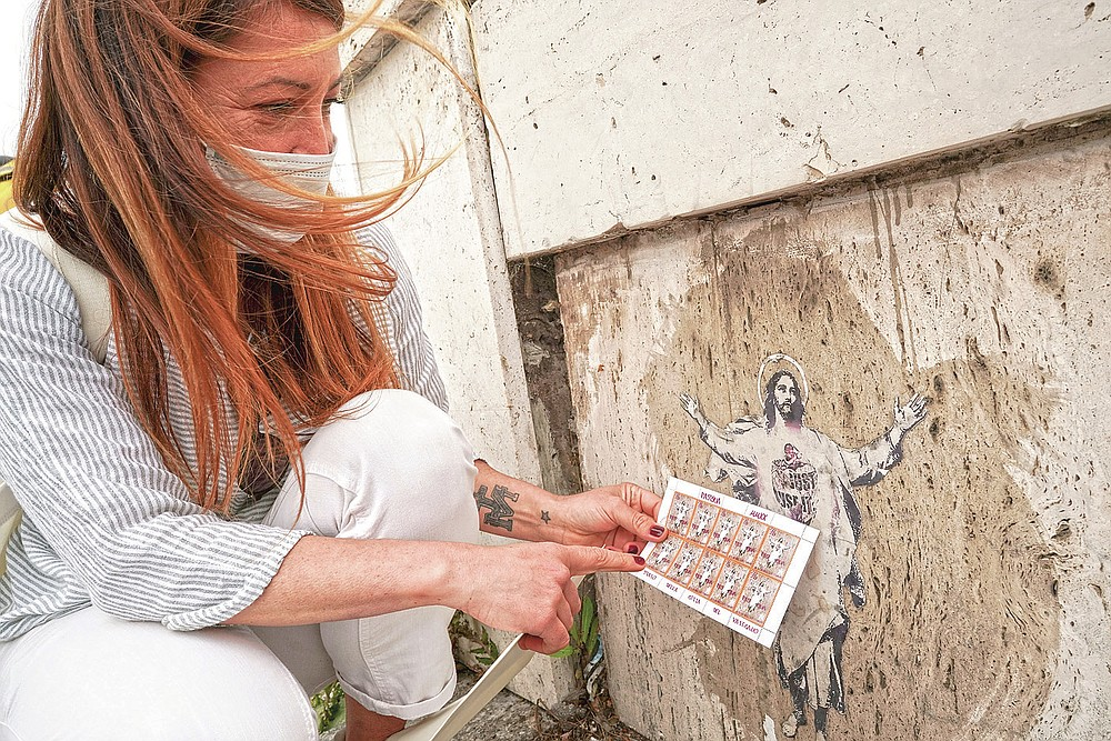 Artist Alessia Babrow holds the Vatican stamps next to her street art during an interview with the Associated Press, at the Vatican, Friday, May 14, 2021. One night in early 2019, Rome street artist Babrow glued a stylized image of Christ she had made to a bridge near the Vatican. A year later, she was shocked to learn that the Vatican had used her image, featuring her hallmark heart emblazoned across Christ's chest, as its 2020 Easter postage stamp.  (AP Photo/Andrew Medichini)
