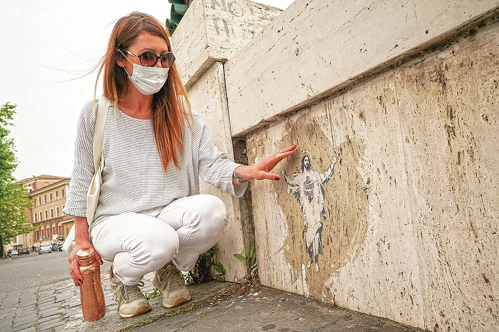 Artist Alessia Babrow shows her street art during an interview with the Associated Press, at the Vatican, Friday, May 14, 2021. One night in early 2019, Rome street artist Alessia Babrow glued a stylized image of Christ she had made to a bridge near the Vatican. A year later, she was shocked to learn that the Vatican had used her image, featuring her hallmark heart emblazoned across Christ's chest, as its 2020 Easter postage stamp.  (AP Photo/Andrew Medichini)