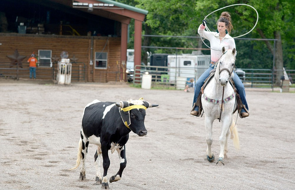 Marc Hayot/Siloam Sunday Kelli Cripps-Tully raised her lasso as she prepares to rope a young steer as it runs to the other side of the arena