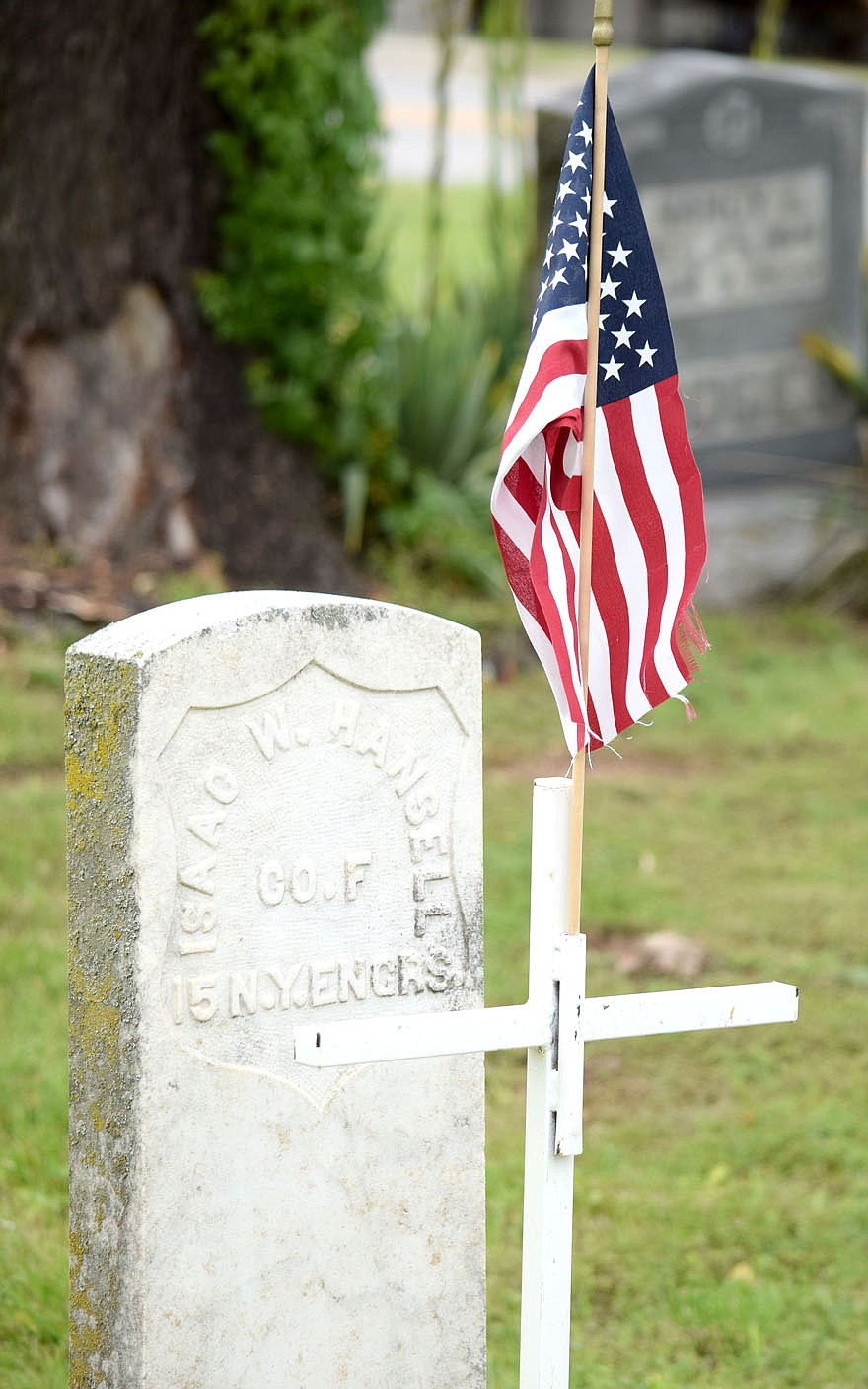 Westside Eagle Observer/MIKE ECKELS During the 2021 Memorial Day observance in Decatur Saturday morning, a cross and American flag adorns the head stone of Isaac W. Hansell, Union Army soldier with the 15th New York Engineers who died sometime during the Civil War. Hansell was one of 134 military veterans buried in the Decatur Cemetery to receive the cross and flag in remembrance of their sacrifice in defense of freedom.