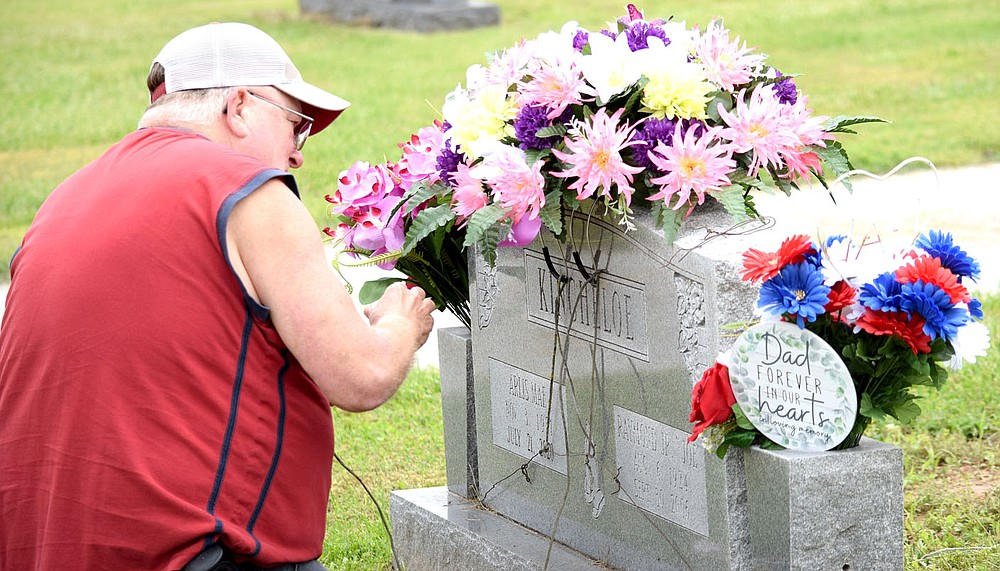 Westside Eagle Observer/MIKE ECKELS A family member adjusts the flowers on Arlis Mae Kincheloe's headstone as other family members gathered at Decatur Cemetery Saturday morning to remember their loved ones. Families gathered Memorial Day to remember this country's veterans who made the ultimate sacrifice in defense of our freedom.