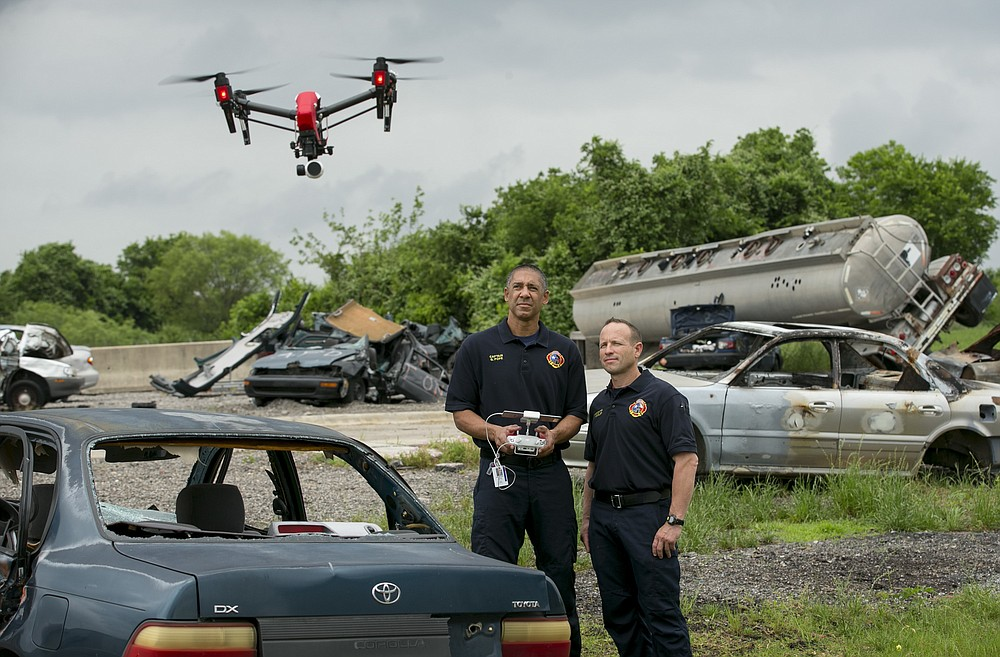 FILE - In this April 20, 2017 file photo, Austin Fire Department Capt. Greg Pope, left, and firefighter Coitt Kessler demonstrate flying a DJI Inspire 1 drone at the Austin Fire Department Training Academy in Austin, Texas.  More than a year after the U.S. Interior Department grounded hundreds of Chinese-made drones it was using to track wildfires and monitor dams and wildlife, the future of drone use by the federal government remains unmapped. The latest complication: Legislation moving through Congress that would block the U.S. government from using drones made in China. (Jay Janner/Austin American-Statesman via AP)