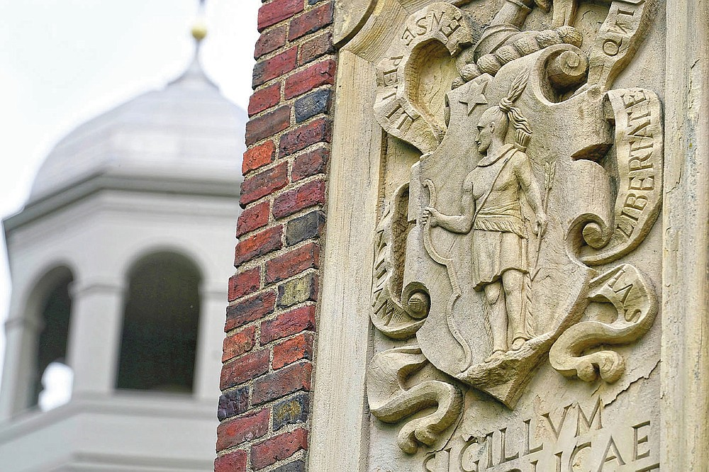 """An image of a Native American, right, is featured in the artwork of Johnston Gate, Harvard University's first and largest gate heading to the campus, in Cambridge, Mass., Sunday, May 23, 2021. Some 350 years ago, Caleb Cheeshahteaumuck, an Aquinnah Wampanoag man, became the first Native American to graduate from the university, the product of Harvard's chartered mission to educate """"English and Indian youths of this country."""" (AP Photo/Steven Senne)"""