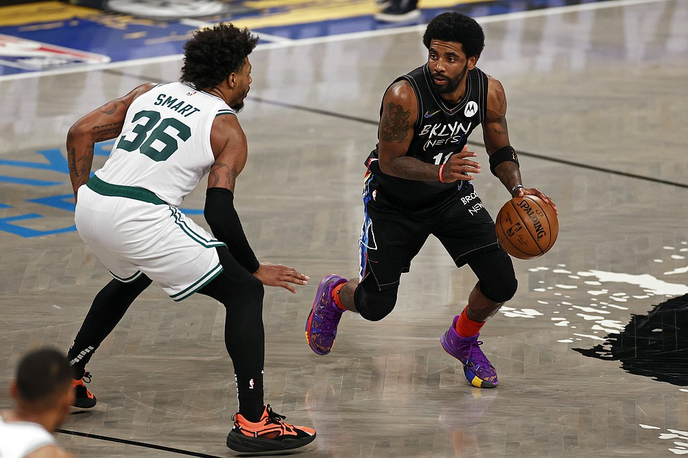 Brooklyn Nets guard Kyrie Irving, right,  drives around Boston Celtics guard Marcus Smart, left, in the second half of Game 5 during an NBA basketball first-round playoff series, Tuesday, June 1, 2021, in New York. (AP Photo/Adam Hunger)