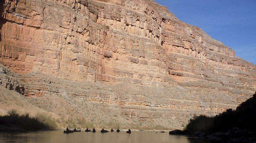Nine of the 12 canoes are visible in April 2021 as they float the San Juan River through Slickhorn Canyon in southeast Utah. Sixteen people, including 12 canoes and a raft carrying four, paddled 83.5 miles of the San Juan River from the Sand Island Boat Ramp near Bluff, Ut., to Clay Hills Crossing UT.. Check out nwaonline.com/210608Daily/ and nwadg.com/photos for a photo gallery. (NWA Democrat-Gazette/David Gottschalk)