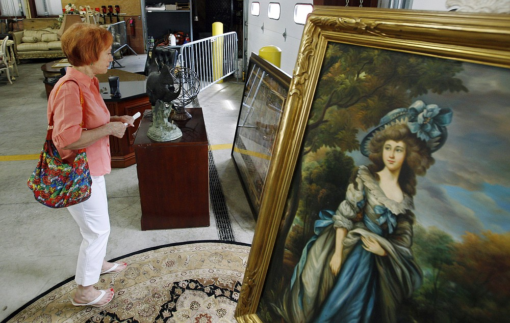 FILE - Reenie Harris of Cedar Knolls, N.J., admires a large framed antique print during a public viewing, of items to be auctioned from the home of former Bernard Madoff finance chief Frank DiPascali, Thursday, June 24, 2010, in Morris Plains, N.J. The U.S. Marshals Service in New Jersey auctioned 51 lots of items that belonged to DiPascali, one of Madoff's closest associates. More than 12 years after Madoff confessed to running the biggest financial fraud in Wall Street history, a team of lawyers is still at work on a sprawling effort to recover money for the thousands of victims of his scam. (AP Photo/Mel Evans, File)