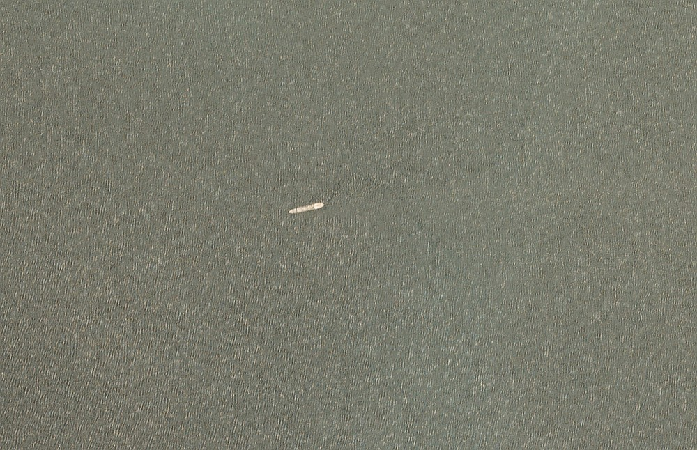 In this satellite image provided by Planet Labs Inc. the Iranian navy's Kharg support ship is seen off the coast of Jask, Iran, Tuesday, June 1, 2021. The Kharg, the largest ship in the Iranian navy, caught fire and later sank Wednesday, June 2, 2021 in the Gulf of Oman under unclear circumstances, semiofficial news agencies reported. (Planet Labs Inc. via AP)