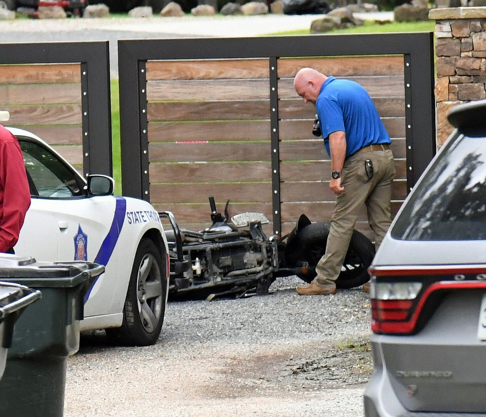 An Arkansas State Police investigator looks over an abandoned motorcycle believed to belong to a fleeing suspect at 614 Woodview Lane on Wednesday. - Photo by Tanner Newton of The Sentinel-Record