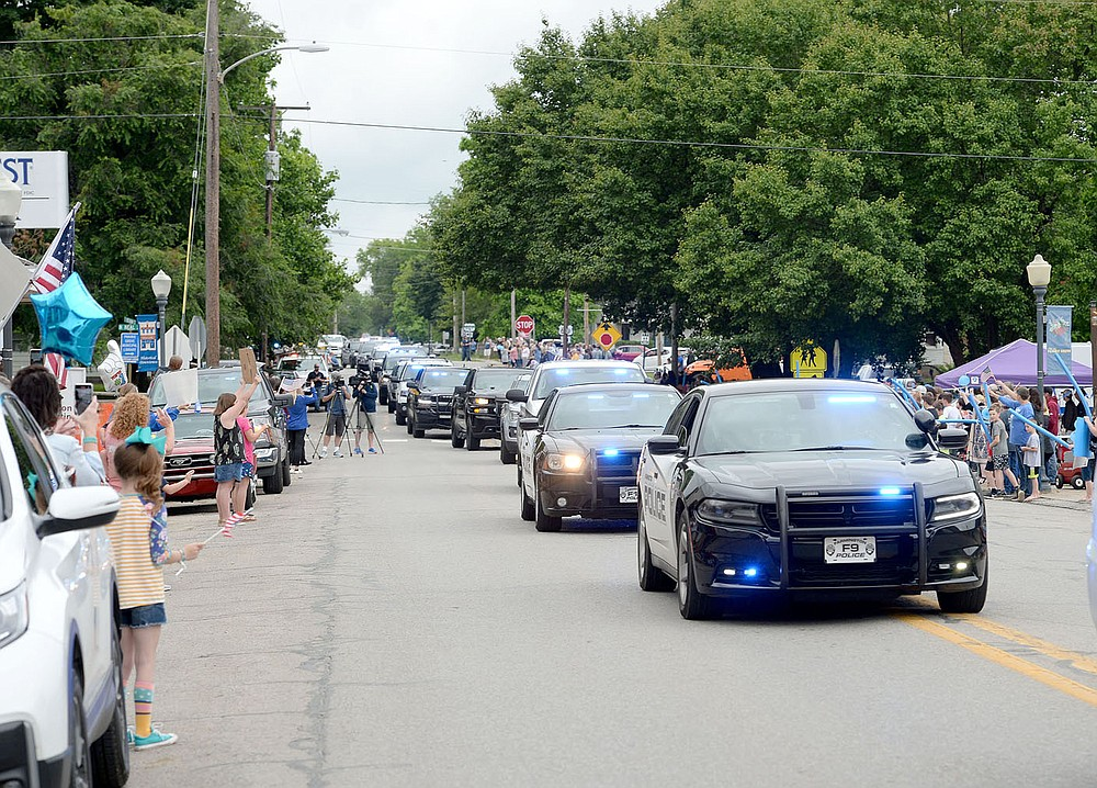 ANDY SHUPE NWA DEMOCRAT-GAZETTE A long line of law enforcement vehicles from across Northwest Arkansas makes its way Wednesday, June 2 through downtown Prairie Grove during a parade to welcome home Tyler Franks, an officer with the Prairie Grove Police Department who was shot May 4 while responding to a domestic disturbance. One observer said the parade included 75 vehicles from 15 agencies.