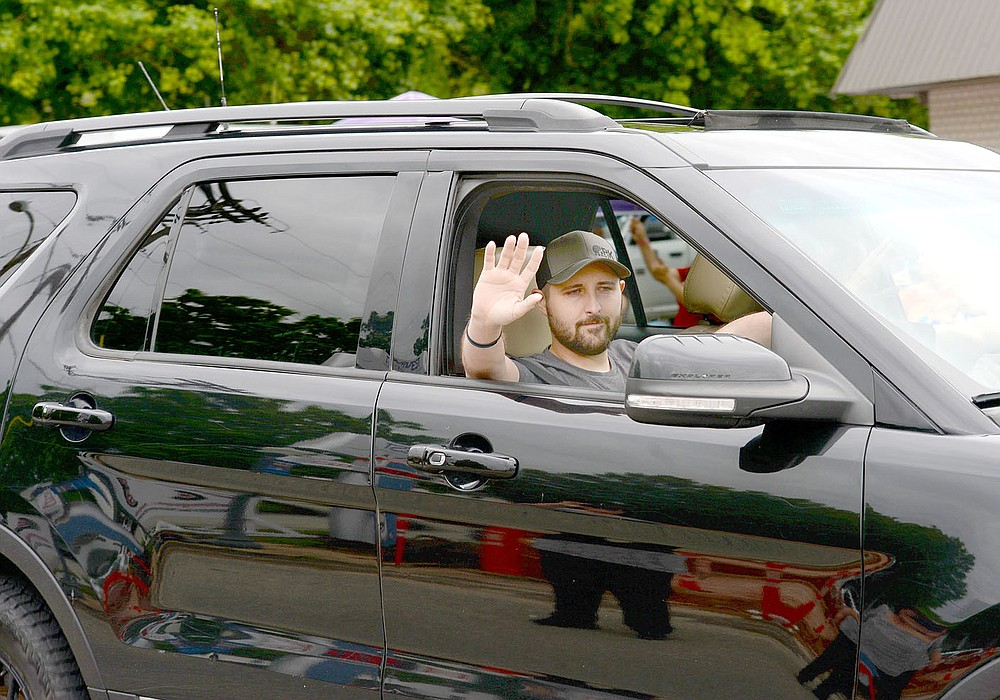 ANDY SHUPE NWA DEMOCRAT-GAZETTE Tyler Franks, an officer with Prairie Grove Police Department, waves at the crowd June 2 during a parade held in his honor and to welcome him home. Franks was shot May 4 while responding to a domestic disturbance.