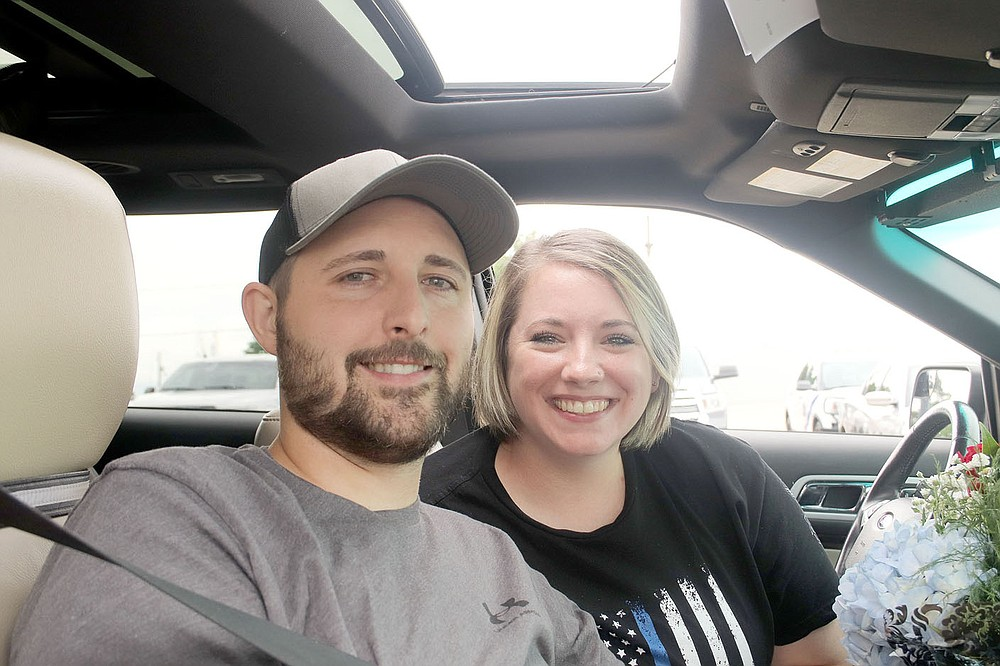 """LYNN KUTTER ENTERPRISE-LEADER Prairie Grove Police Officer Tyler Franks and his wife, Amber, meet with the media, friends, family and the community in the library parking lot following a """"Welcome Home"""" parade in his honor on June 2."""
