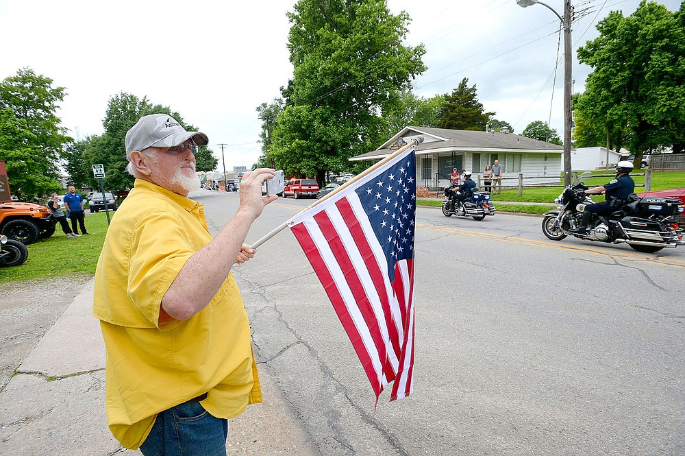 ANDY SHUPE NWA DEMOCRAT-GAZETTE  Residents hold flags and signs Wednesday, June 2, 2021, during a parade in downtown Prairie Grove to welcome home Tyler Franks, an officer with the Prairie Grove Police Department who was shot May 4 while responding to a domestic disturbance.