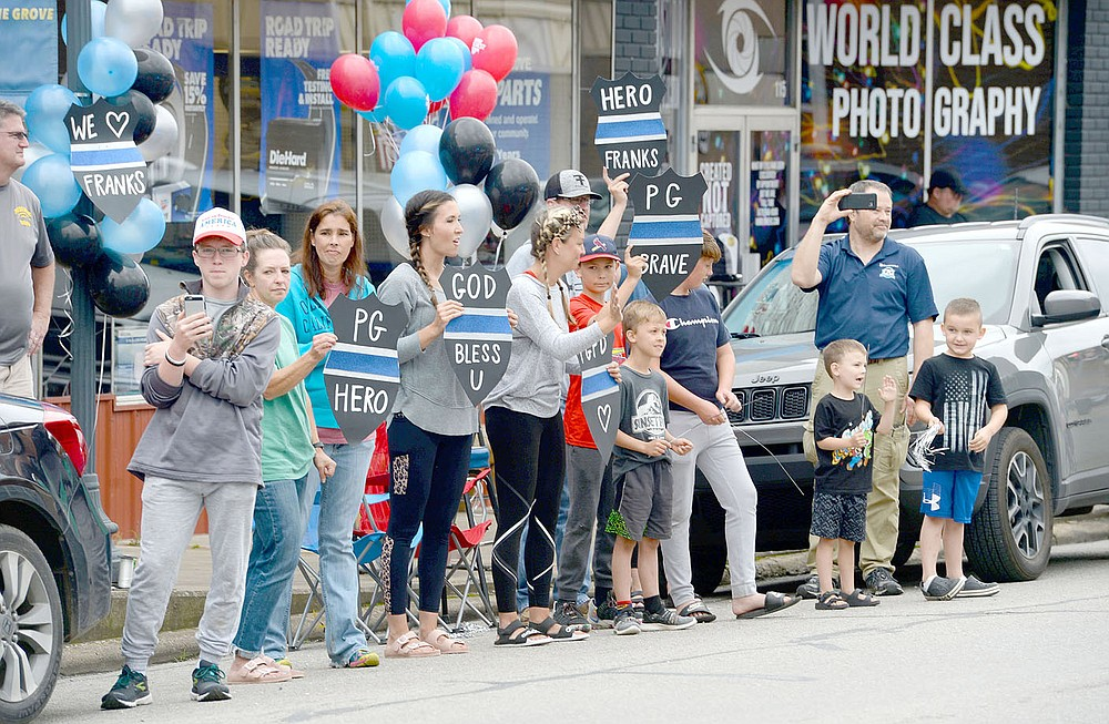 ANDY SHUPE NWA DEMOCRAT-GAZETTE Residents hold signs Wednesday, June 2, during a parade in downtown Prairie Grove to welcome home Tyler Franks, an officer with the Prairie Grove Police Department who was shot May 4 while responding to a domestic disturbance.