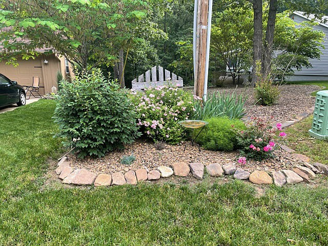 Photo submitted There is a beautiful side yard with plenty of trees forming a beautiful oasis with a bench.