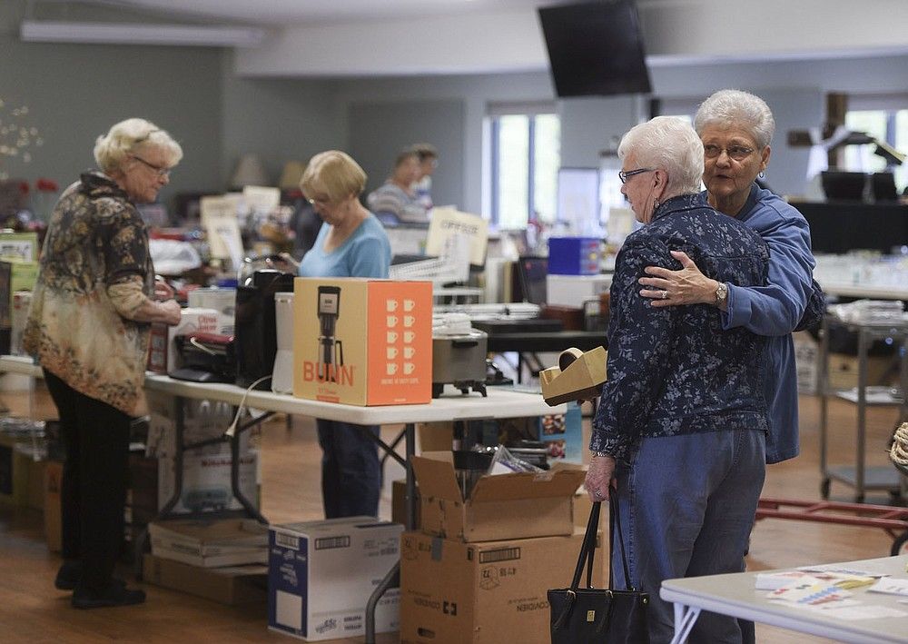 NWA Democrat-Gazette/CHARLIE KAIJO Suzanne Evans of Bella Vista (right) greets Glenda Redenius of Bella Vista during the setup of a flea market, Thursday, April 25, 2019 at Highlands Church of Bella Vista in Bella Vista.   The church is having their 25th annual flea market. All of the market's proceeds will go to benefit Benton County charities including the NWA Children's Shelter, the NWA Women's Shelter and Samaritan's feet to name a few.