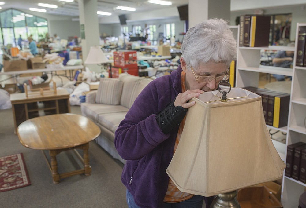 NWA Democrat-Gazette/CHARLIE KAIJO Patricia Lehman of Bella Vista changes the bulb of a lamp for sale during the setup of a flea market, Thursday, April 25, 2019 at Highlands Church of Bella Vista in Bella Vista.   The church is having their 25th annual flea market. All of the market's proceeds will go to benefit Benton County charities including the NWA Children's Shelter, the NWA Women's Shelter and Samaritan's feet to name a few.