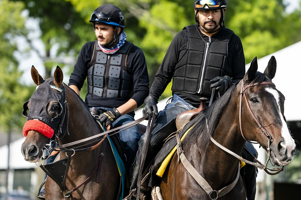 Belmont stakes entrant Hot Rod Charlie, left, and his companion horse Lava Man, right, are led to the main track for a training run ahead of the 153rd running of the Belmont Stakes horse race, Wednesday, June 2, 2021, at Belmont Park in Elmont, N.Y. (AP Photo/John Minchillo)