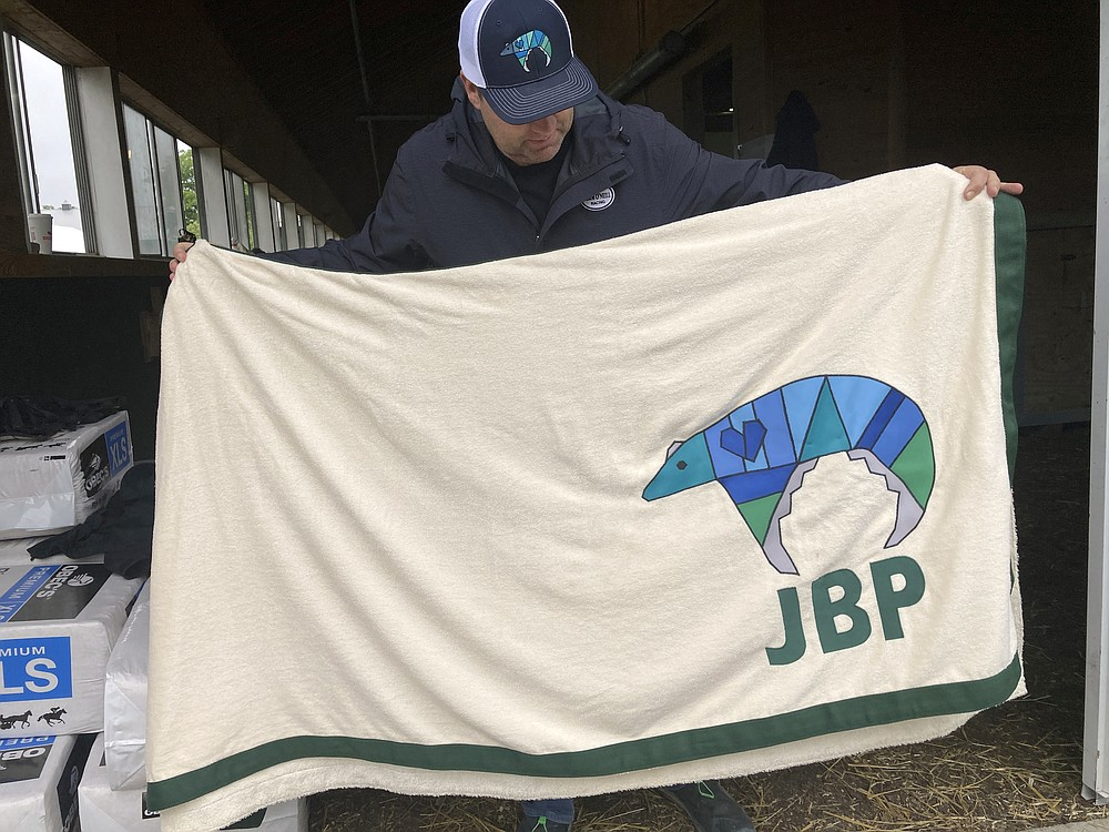 Trainer Doug O'Neill holds up the saddle cloth for Belmont Stakes entrant Hot Rod Charlie at Belmont Park, Thursday, June 3, 2021 , in Elmont, N.Y., featuring the initials of Jake Panus, who was killed in a car crash last year at age 16. O'Neill and some of Hot Rod Charlie's owners have embraced Panus' memory. (AP Photo/Stephen Whyno)