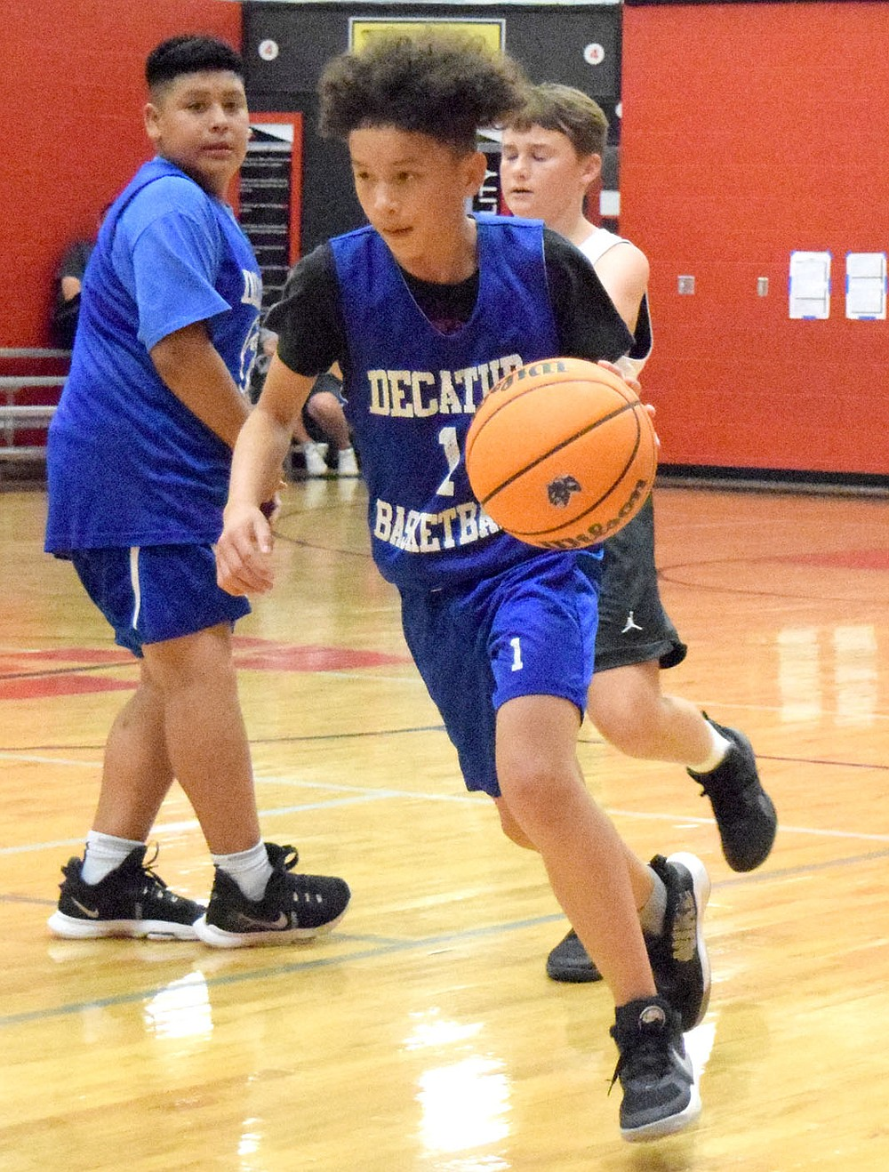 Westside Eagle Observer/MIKE ECKELS Alan Medel (left) puts up a perfect screen which allowed Ricky Thor (center) to get around a Maverick defender during the June 8 junior high contest between Decatur and Fort Smith Southside in Fayetteville. The Mavericks took the win in the Arkansas Athletics Outreach team camp 26-4 over the Bulldogs.