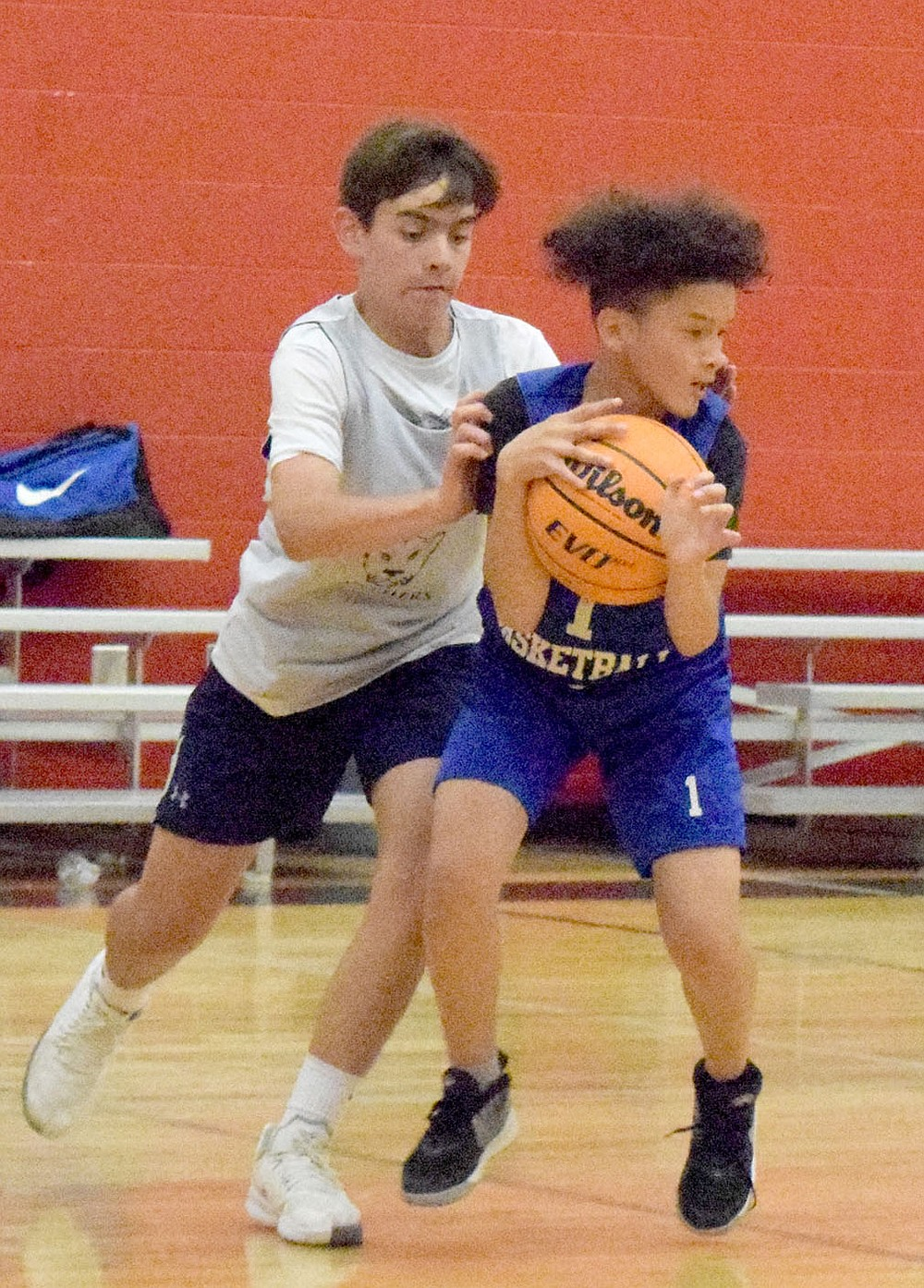 Westside Eagle Observer/MIKE ECKELS Ricky Thor (1) latches onto a loose ball and holds on, keeping it out of the reach of a Panther player during the June 8 Decatur- St. Joseph Catholic junior high basketball contest in Fayetteville. The Panthers took the win 19-15 during the Arkansas Athletics Outreach team camp.