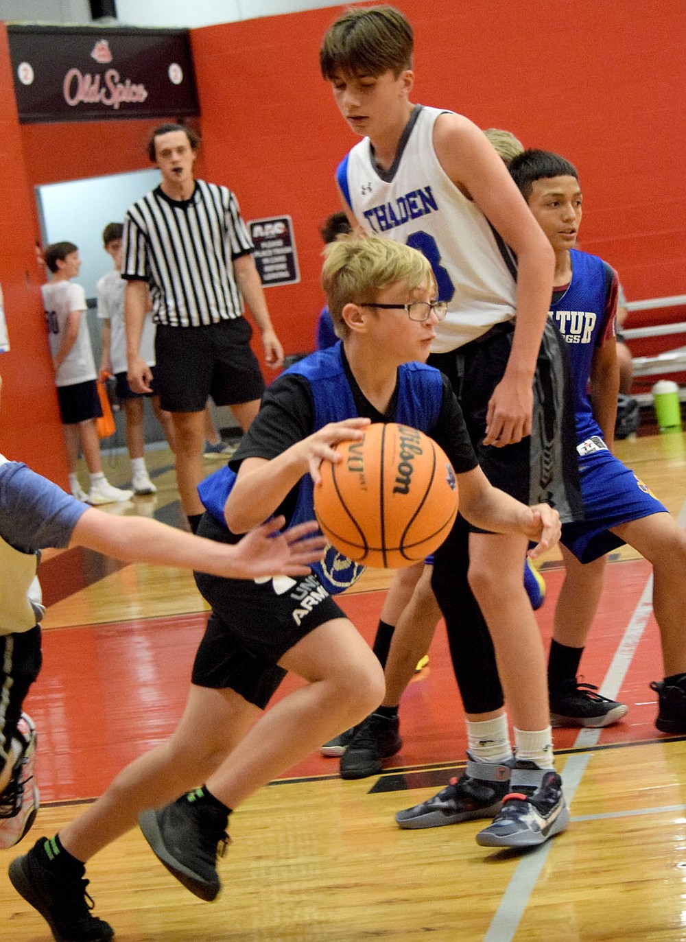 Westside Eagle Observer/MIKE ECKELS After pulling down a rebound, Devin Pembleton (center) drives toward the Bulldog net during the Decatur-Thaden junior high basketball contest on court number 2 at the Arkansas Athletics Outreach team camp in Fayetteville June 8. The junior high team took the 22 minute contest 21-17.