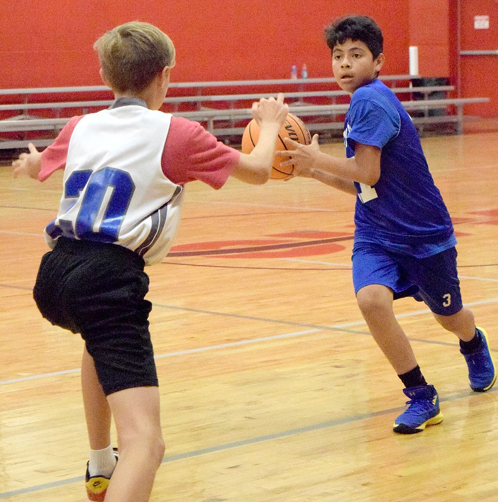 Westside Eagle Observer/MIKE ECKELS John Colorado (right) looks for a teammate to pass the ball to during the second half of the Decatur-Thaden junior high basketball game in Fayetteville June 8. The Decatur boys participated in the 2021 Arkansas Athletics Outreach team camp where the team claimed the win 21-17.