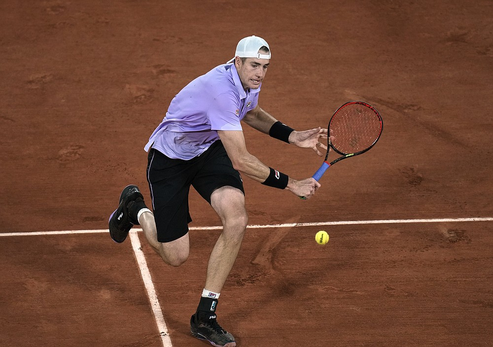 United States' John Isner plays a return to Stefanos Tsitsipas of Greeceday during their third round match on 6, of the French Open tennis tournament at Roland Garros in Paris, France, Friday, June 4, 2021. (AP Photo/Christophe Ena)