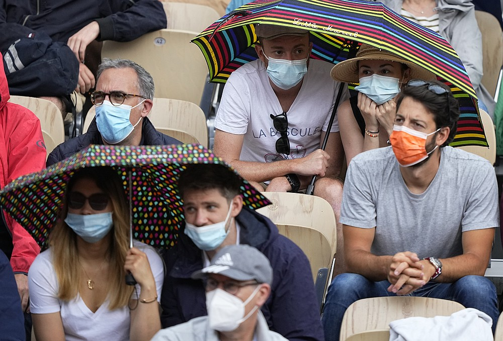 Spectators on the Simonne Mathieu court put up umbrellas as rain falls while they watch Japan's Kei Nishikori play against Switzerland's Henri Laakosonen during their third round match on day 6, of the French Open tennis tournament at Roland Garros in Paris, France, Friday, June 4, 2021. (AP Photo/Michel Euler)