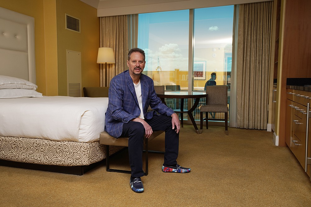 """Lane Blue sits for a portrait in a condo he bought in the Trump International Hotel Las Vegas, Saturday, May 22, 2021, in Las Vegas. """"They're giving them away,"""" says Blue who paid $160,500 in March for a studio in Trump's Las Vegas tower, $350,000 less than the seller had paid in 2008. It was his second purchase in the building this year and may not be his last. """"I'm thinking of picking up another one."""" (AP Photo/John Locher)"""