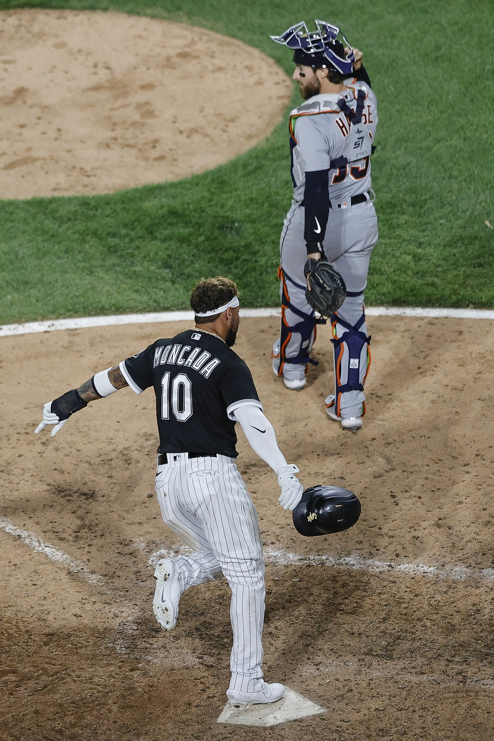 Chicago White Sox's Yoan Moncada (10) scores on a single hit by Yermin Mercedes off Detroit Tigers relief pitcher Jose Cisnero during the ninth inning of a baseball game, Friday, June 4, 2021, in Chicago. (AP Photo/Kamil Krzaczynski)