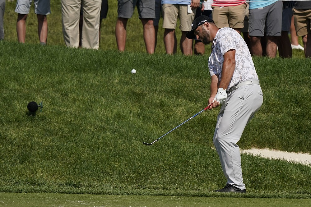 Jon Rahm chips to the 14th green during the third round of the Memorial golf tournament, Saturday, June 5, 2021, in Dublin, Ohio. Rahm was later notified he tested positive for the coronavirus, knocking him out of the tournament.  (AP Photo/Darron Cummings)
